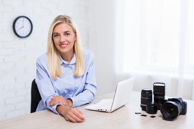 Photographe professionnel de jeune femme avec l'ordinateur d'appareil-photo et l'équipement de photographie