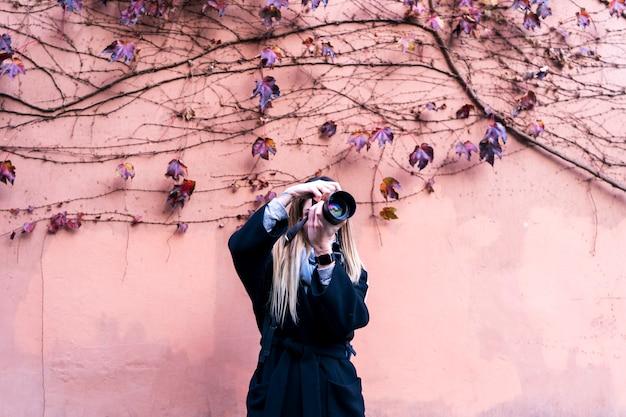 Photographe professionnel prenant des photos sur du rose pastel