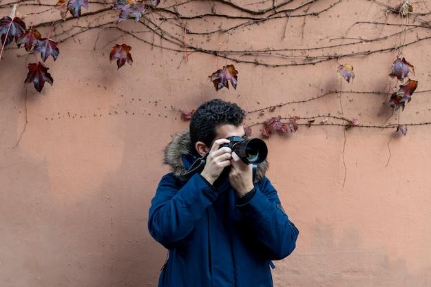 Photographe professionnel prenant des photos sur l'orange pastel