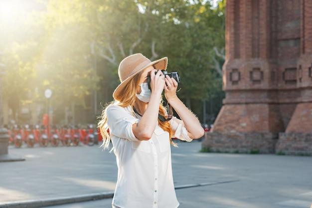 Photographe professionnel voyageant et prenant des photos avec un masque facial à l'extérieur