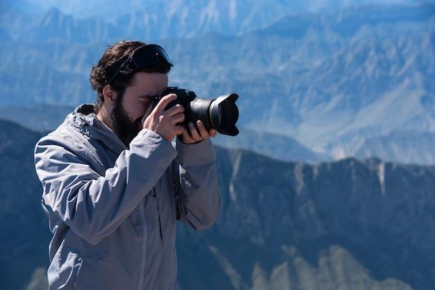Photographe randonneur prenant une photo au sommet de la montagne. voyage style de vie et concept d'aventure