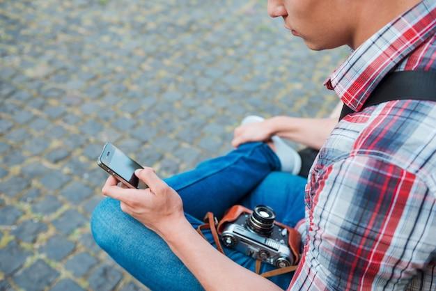Photographe relaxant. gros plan sur un jeune photographe avec un appareil photo à l'ancienne en train de taper quelque chose sur son téléphone portable alors qu'il était assis à l'extérieur