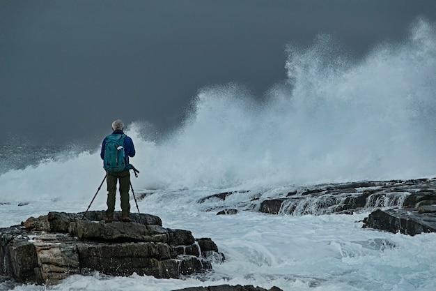 Photographe sur les rochers en mer orageuse