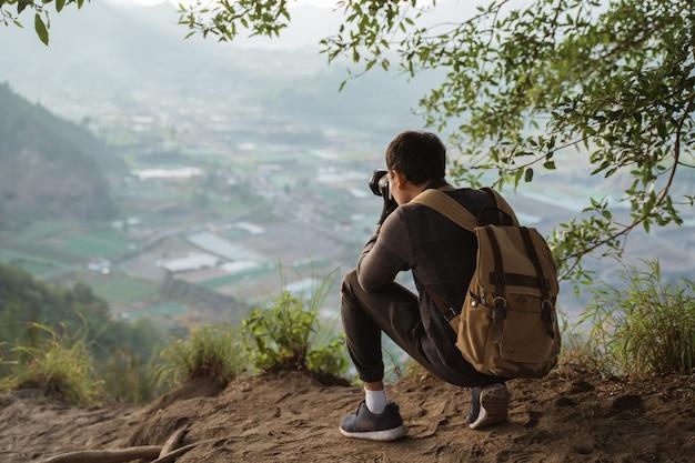 Photographe avec sac à dos et appareil photo prenant des photos de montagnes