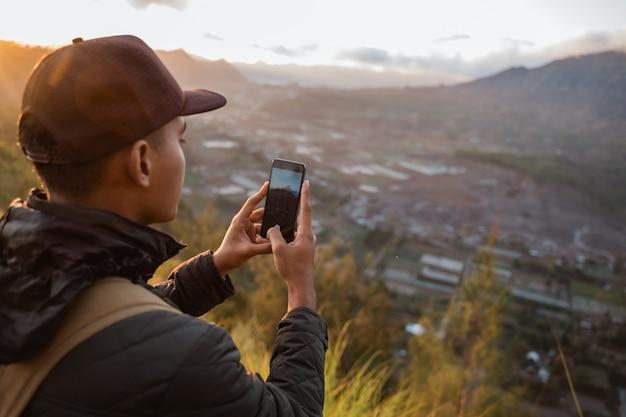 Photographe avec sac à dos et téléphone prenant des photos de montagnes