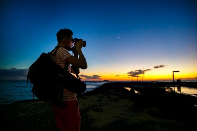 Le photographe se tient debout avec une caméra sur le rivage avec un beau ciel du soir derrière lui