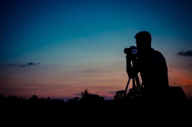 Photographe de silhouette avec fond de coucher de soleil