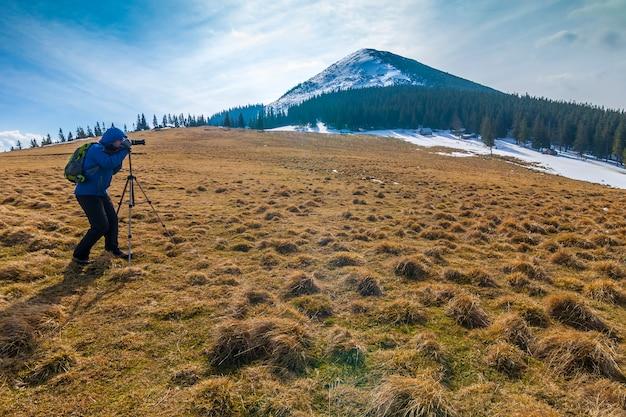 Photographe solitaire dans les montagnes avec un appareil photo sur un trépied par temps froid