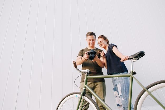Photographe souriant et femme heureuse, vérification des photos après la prise de vue, debout avec vélo rétro sur mur blanc. en plein air.