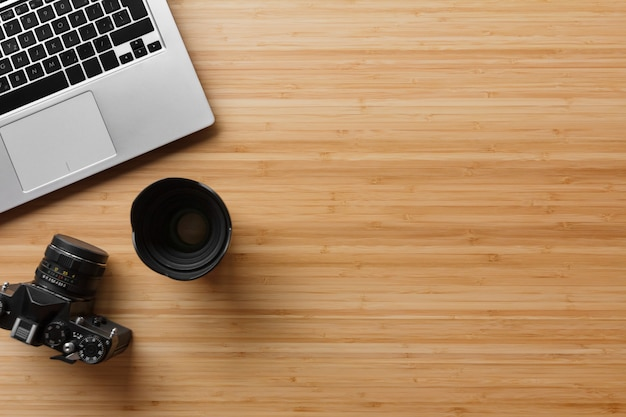 Photographe table de bureau en bambou avec appareil photo argentique, ordinateur portable et fond de fournitures. vue de dessus, mise à plat, espace de copie.
