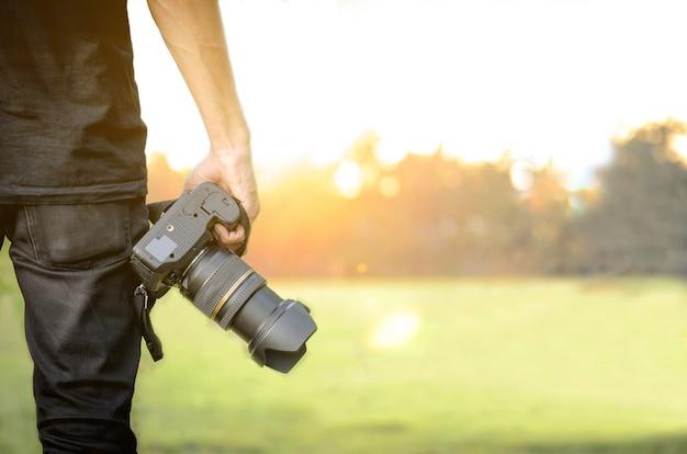 Photographe tenant un appareil photo à la main sur fond de coucher de soleil