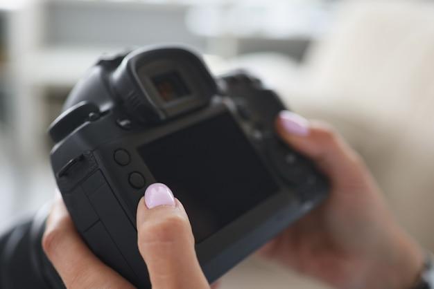 Le photographe tient la caméra dans ses mains en gros plan