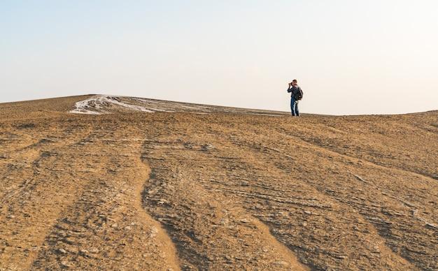 Photographe touriste sur un volcan de boue