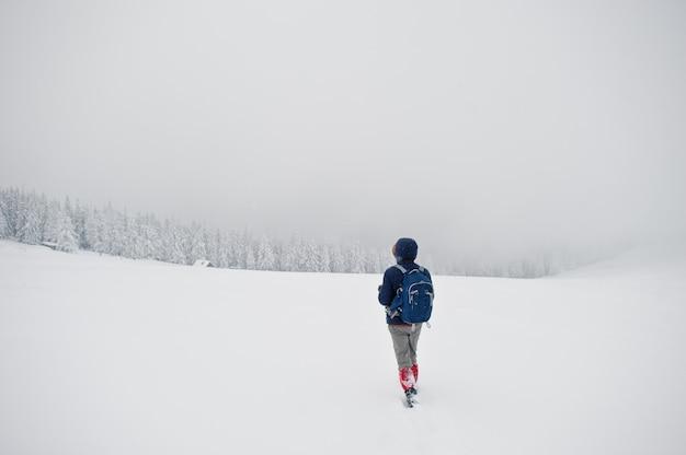 Photographe touristique homme avec sac à dos, à la montagne avec des pins recouverts de neige