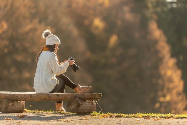 Une photographe en vêtements chauds prend des photos de la nature à l'extérieur, assise sur un banc en bois.