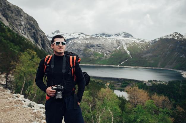 Photographe ou voyageur utilisant un appareil photo reflex numérique professionnel dans la nature