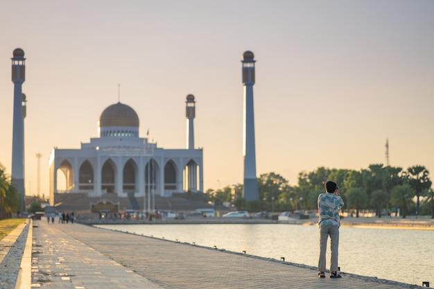 Des photographes attendent de prendre des photos d'une mosquée dans la soirée.