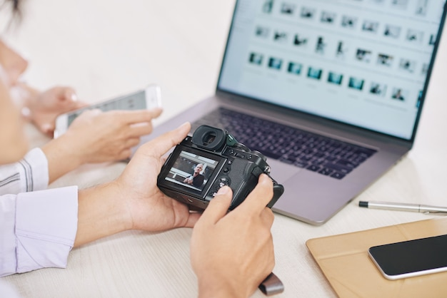 Photographes de cultures avec ordinateur portable et appareil photo