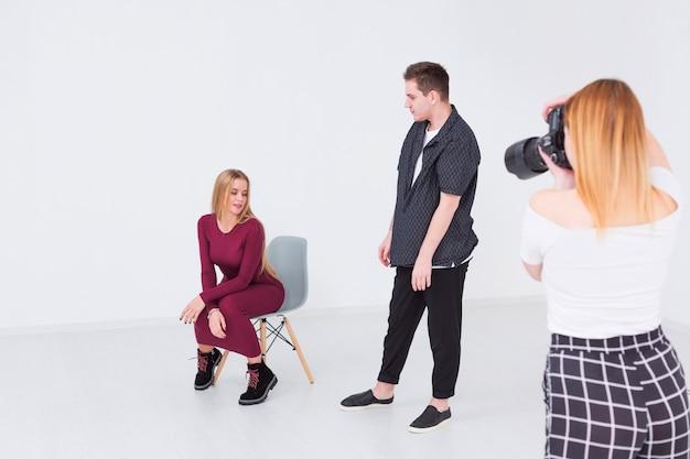Photographes et modèles prenant des photos dans un studio