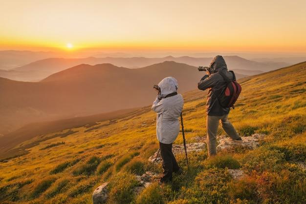 Les photographes prennent un coucher de soleil dans les montagnes