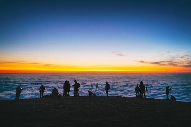 Les photographes touristes en haute montagne prennent des photos du soleil levant au-dessus des nuages