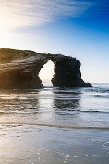 Photographie d'arches formées par les falaises de la plage