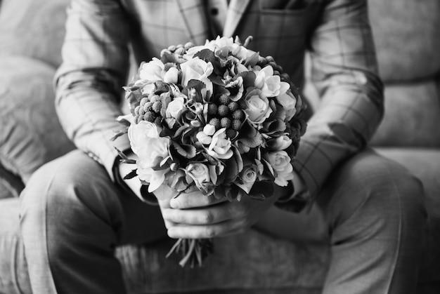 Photographie d'art noir et blanc monochrome, marié en costume tenant un bouquet de fleurs. boutonnière de mariage