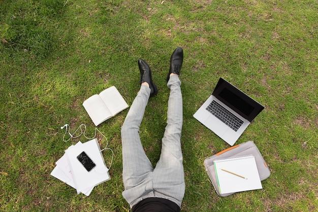 Photographie artistique d'un étudiant avec ordinateur portable et notes