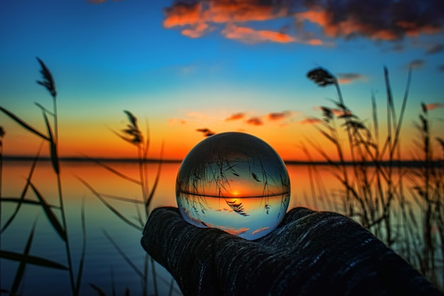 Photographie de boule de lentille de cristal créative d'un lac avec de la verdure autour à l'aube