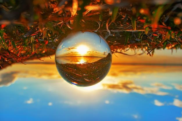 Photographie de boule de lentille de cristal créative de verdure et d'un lac au coucher du soleil