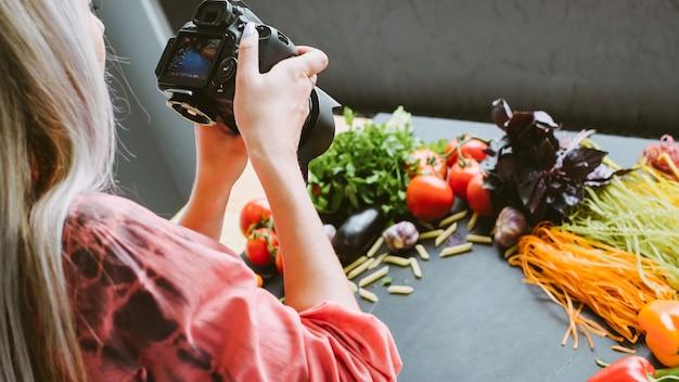 Photographie culinaire. promotion des restaurants italiens. styliste féminine tirant des ingrédients de pâtes biologiques.