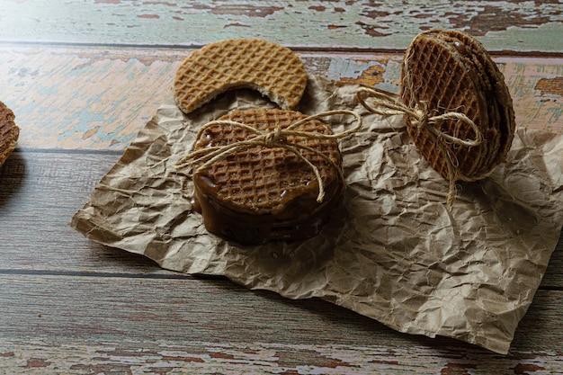 Photographie discrète. empiler des stroopwafels avec un arc en sisal, à côté d'un autre biscuit avec une bouchée.