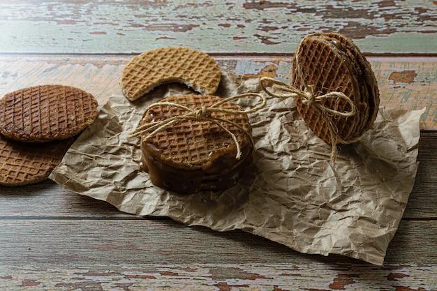 Photographie discrète. empiler des stroopwafels avec une boucle de sisal, aux côtés d'autres cookies.