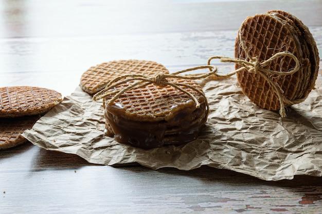 Photographie discrète. empiler des stroopwafels avec une boucle de sisal, à côté d'autres cookies (vue latérale).