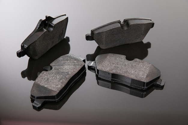 Photographie d'image de plaquettes de frein sur un fond noir et gris