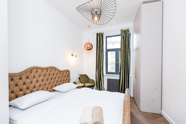 Photographie d'intérieur grande chambre avec lit blanc dans un style moderne