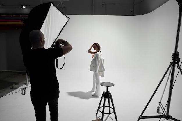 Photographie de mode dans un studio photo. photographe professionnel de sexe masculin prenant des photos d'un modèle de belle femme à l'appareil photo, dans les coulisses