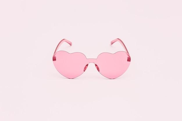 Photographie de mode de style minimal avec des lunettes en forme de coeur sur rose
