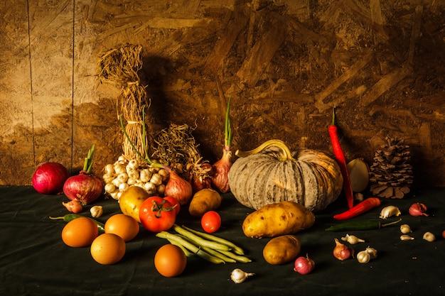 Photographie de nature morte avec citrouille, épices, herbes, légumes et fruits.