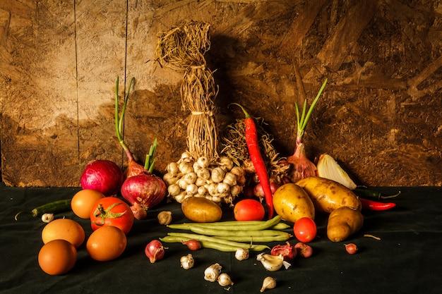 Photographie de nature morte avec des épices, des herbes, des légumes et des fruits.