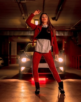 Photographie avec néon rouge devant une voiture dans un parking. portrait d'une jolie jeune femme blonde de race blanche