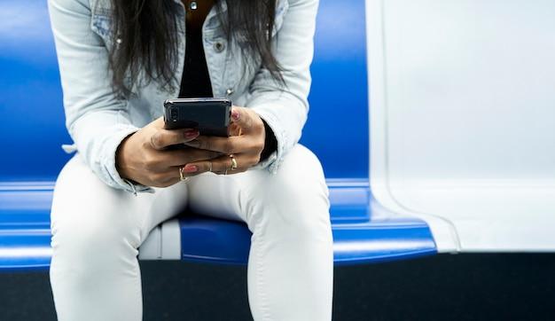 Photographie panoramique des mains d'une femme méconnaissable assise dans la voiture de métro à l'aide d'un smartphone.