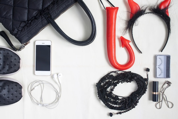 Photographie plat avec accessoires halloween, produits cosmétiques, articles essentiels pour femme et smartphone, vue aérienne des articles accessoires halloween, vue de dessus