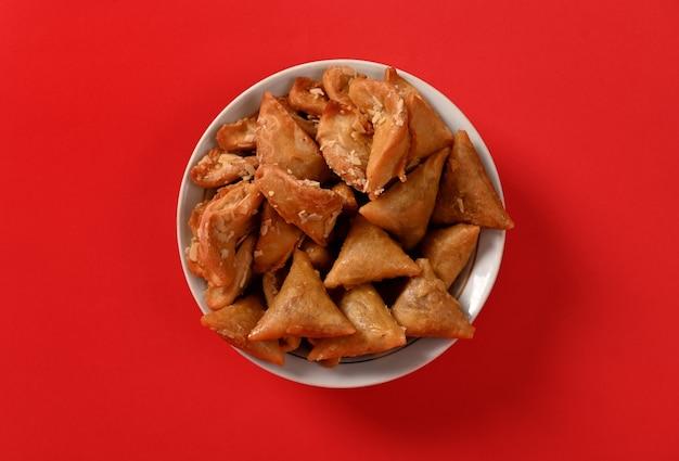 Photographie à plat d'une assiette délicieuse et sucrée pleine de bonbons brewat faits à la main marocains traditionnels luxueux, isolés sur fond rouge.