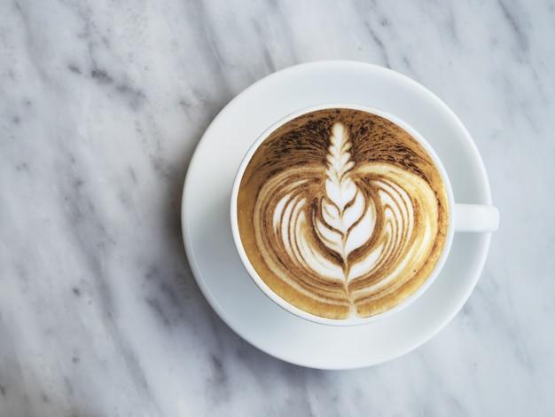 Photographie de plat laïde de café avec art latte magnifique sur fond de marbre blanc.