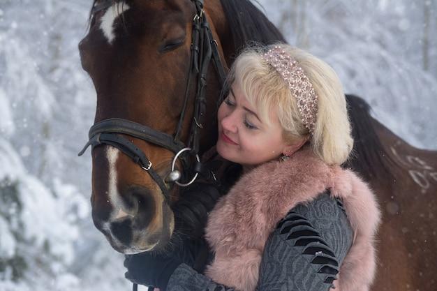 Photographie de portrait d'une femme et d'un cheval se bouchent.