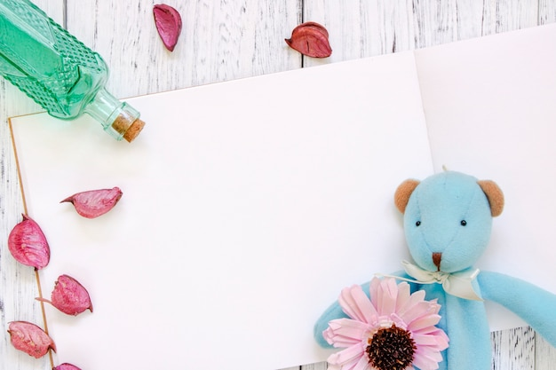 La photographie de stock plat poser vintage blanc peint en bois table pétales de fleurs pourpres ours poupée bouteille en verre vert