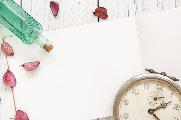 Photographie de stock plat poser vintage blanc peint en bois table pétales de fleurs pourpres réveil vintage bouteille en verre vert