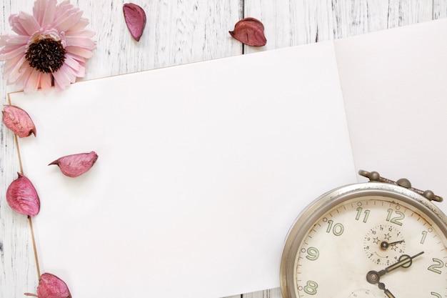 Photographie de stock plat poser vintage blanc peint en bois table pourpre pétales de fleurs vintage réveil