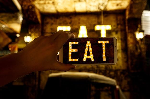 Photographie sur téléphone portable. image du mot manger écrit par des ampoules.